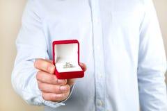 Сцена предложения захвата/замужества/свадьбы Закройте вверх человека вручая дорогое кольцо с бриллиантом платины золота к его нев Стоковая Фотография
