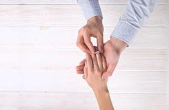 Сцена предложения захвата/замужества/свадьбы Закройте вверх человека вручая дорогое кольцо с бриллиантом платины золота к его нев Стоковое Изображение RF