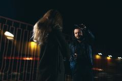 Сцена разбойничества улицы ночи: человек принимая отсутствующую молодую женскую сумку стоковые фото