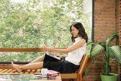 Сцена утра сочинительства молодой женщины правого на тетради около окна в кафе Образ жизни Freelance работая стоковое фото rf