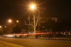 Сцена улицы на ноче в городском городке, светлые следы автомобиля освещает Стоковые Изображения