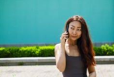 Счастливая азиатская девушка говоря над мобильным телефоном пока просыпающ в улице стоковое изображение rf