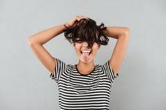 Счастливая азиатская девушка играя с ее волосами и показывая язык стоковые фото