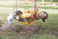 Счастливая азиатская девушка маленького ребенка имея потеху, который нужно сыграть на качании Стоковые Фото