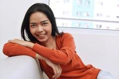 Счастливая азиатская женщина при сторона улыбки сидя на кресле Стоковое Фото