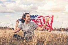 Счастливая азиатская женщина с американским флагом США отпраздновать 4-ое -го июль стоковые изображения rf