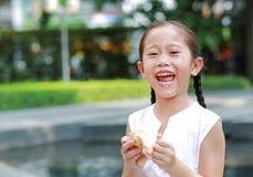 Счастливая азиатская маленькая девочка есть хлеб с заполненным наполненным Клубник десертом и запятнанный вокруг ее рта в саде на стоковая фотография