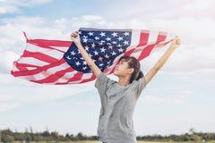 Счастливая азиатская маленькая девочка с американским флагом США отпраздновать 4-ое -го июль стоковое изображение