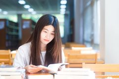 Счастливая азиатская молодая женщина студента думая с книгой в библиотеке стоковое изображение rf