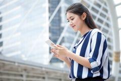 Счастливая азиатская молодая коммерсантка говоря на мобильном телефоне в городском городе напольно стоковые изображения