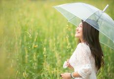Счастливая азиатская рука образа жизни женщины держа зонтик в восходе солнца цветка желтого цвета луга Активные внешние ослабляют стоковая фотография