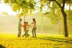 Счастливая азиатская семья играя на поле Стоковая Фотография RF