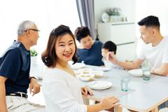 Счастливая азиатская семья из нескольких поколений имея обедающий дома вполне счастья и улыбок стоковое фото rf