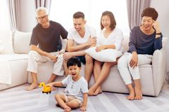 Счастливая азиатская семья из нескольких поколений сидя на софе совместно и наблюдая маленьком ребенке играя игрушку на поле с сч стоковые изображения rf