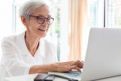 Счастливая азиатская старшая работа женщины, занимаясь серфингом интернет с ноутбуком на таблице в доме, усмехаться престарелый в стоковые фотографии rf