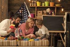 Счастливая американская семья играя с конструктором дома порция матери и отца для того чтобы построить конструкцию с кирпичами стоковые изображения rf