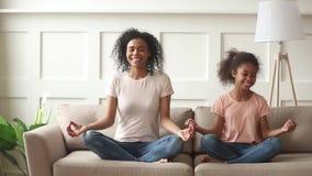 Счастливая африканская дочь ребенк преподавательства мамы делая йогу дома видеоматериал