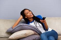 Счастливая Афро-американская девушка держа дистанционное управление сидя на кресле и смотря ТВ Стоковая Фотография RF