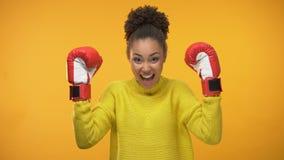 Счастливая Афро-американская женщина в перчатках бокса празднуя успех, чемпион видеоматериал