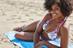 Счастливая афро американская женщина лежа на полотенце на пляже в бикини Стоковая Фотография