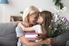 Счастливая бабушка благодаря милую внучку для цветков и gi стоковая фотография rf