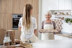 Счастливая бабушка давая испеченные печенья к девушке Стоковая Фотография