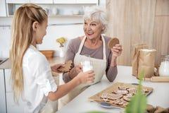 Счастливая бабушка есть испеченное сладостное печенье с внучкой Стоковые Изображения