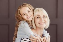 Счастливая бабушка и девушка смотря камеру над коричневой стеной стоковые фотографии rf