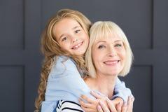 Счастливая бабушка и маленькая внучка прижимаясь внутри помещения стоковое фото