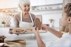 Счастливая бабушка обрабатывая ребенк с сладостным печеньем Стоковые Фото