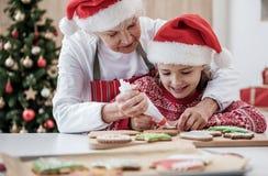 Счастливая бабушка прикладывая сливк на печенье праздника Стоковое Фото