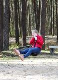Счастливая белокурая девушка подростка одела в красной куртке и голубых джинсах скача и ехать вниз с bungee в спортивной площадке Стоковые Изображения
