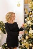Счастливая белокурая девушка широко усмехаясь и представляя против tre рождества стоковое фото