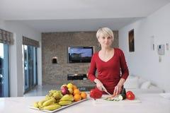 Счастливая белокурая женщина подготовляет еду в кухне Стоковое Изображение RF