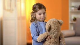 Счастливая белокурая курчавая маленькая девочка играя с любимой плюшевым мишкой, детством стоковые изображения rf