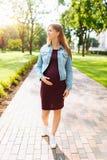 Счастливая беременная девушка идет в парк стоковые фотографии rf