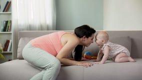 Счастливая беременная женщина играя и имея потеху с жизнерадостным младенцем, сладостное материнство стоковая фотография