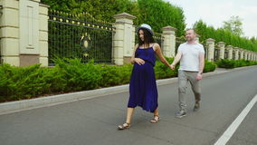 счастливая беременная женщина Она принимает его супруга с ним Усмехаться, идущ совместно в парк акции видеоматериалы