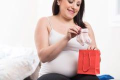 Счастливая беременная женщина смотря носки младенца стоковые изображения rf