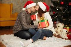 Счастливая беременная женщина с ее шляпами рождества супруга нося Стоковые Изображения RF