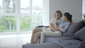 Счастливая беременная, молодая женщина с ободрением говорит мужчины о беременности и кладет руки на живот и будущие улыбки родите видеоматериал