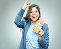 Счастливая бизнес-леди держа пасспорт, кредитную карточку и билет стоковое фото