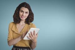 Счастливая бизнес-леди используя таблетку против голубой предпосылки Стоковое Фото