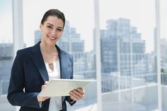 Счастливая бизнес-леди используя таблетку против предпосылки города Стоковое Изображение RF
