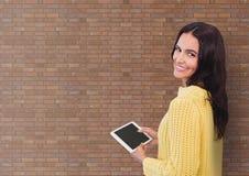 Счастливая бизнес-леди используя таблетку против предпосылки кирпичной стены Стоковые Фото