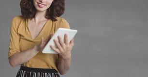 Счастливая бизнес-леди используя таблетку против серой предпосылки Стоковые Изображения RF
