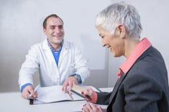 Счастливая более старая дама оплачивая ее счет за медицинские услуги стоковые изображения