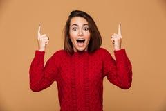 Счастливая выведенная молодая женщина в красном свитере указывая вверх с ребром 2 Стоковые Изображения