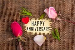 Счастливая годовщина написанная в отверстии на мешковине стоковые изображения