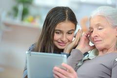 Счастливая грандиозные дочь и бабушка играя с таблеткой Стоковое Фото